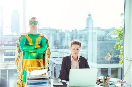 superhero - Superhero standing near businesswoman working in office Stock Photo - Premium Royalty-Free, Code: 6113-07961674