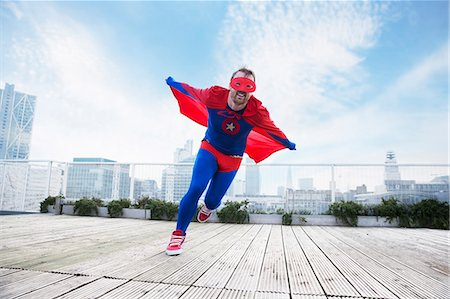superhero - Superhero running with cape on city rooftop Stock Photo - Premium Royalty-Free, Code: 6113-07961675