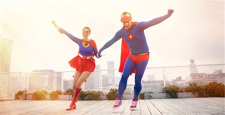 superhero - Superheroes holding hands running on city rooftop Stock Photo - Premium Royalty-Free, Code: 6113-07961678