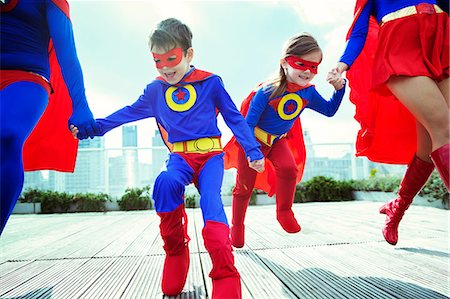 red - Family of superheroes running on city rooftop Stock Photo - Premium Royalty-Free, Code: 6113-07961680