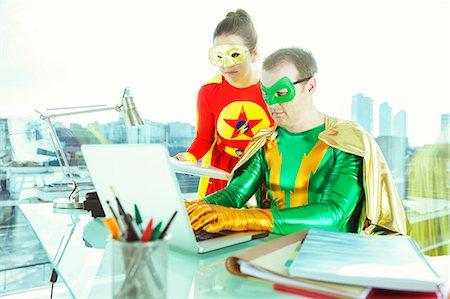 superhero - Superheroes working with laptop in office Stock Photo - Premium Royalty-Free, Code: 6113-07961687