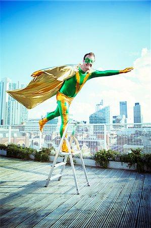 superhero - Superhero posing on stepladder on city rooftop Stock Photo - Premium Royalty-Free, Code: 6113-07961684