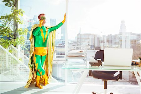 superhero - Superhero talking on cell phone in office Stock Photo - Premium Royalty-Free, Code: 6113-07961693