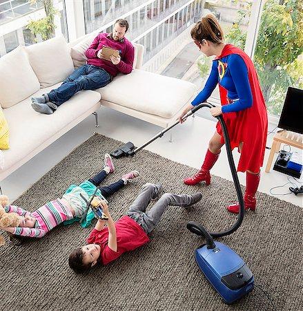Superhero vacuuming around family in living room Stock Photo - Premium Royalty-Free, Code: 6113-07961690
