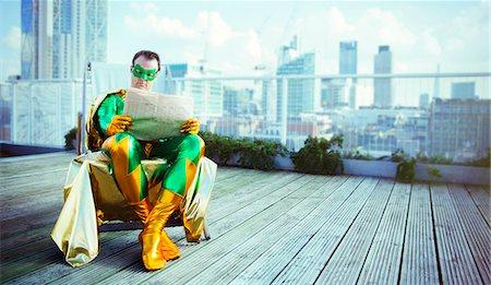 superhero - Superhero reading newspaper on city rooftop Stock Photo - Premium Royalty-Free, Code: 6113-07961691