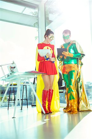 Superheroes working with digital tablet in office Stock Photo - Premium Royalty-Free, Code: 6113-07961697