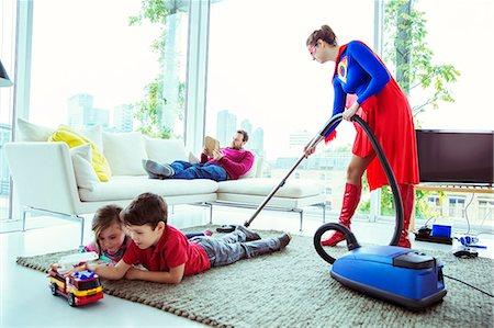 Superhero vacuuming around family in living room Stock Photo - Premium Royalty-Free, Code: 6113-07961694