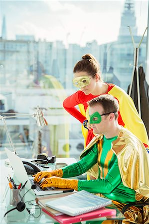 superhero - Superheroes working on laptop in office Stock Photo - Premium Royalty-Free, Code: 6113-07961695