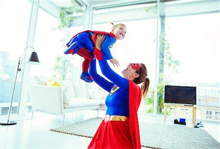 superhero - Superhero playing with baby in living room Stock Photo - Premium Royalty-Free, Code: 6113-07961696