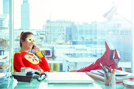 superhero - Superhero talking on cell phone at office desk Stock Photo - Premium Royalty-Free, Code: 6113-07961699