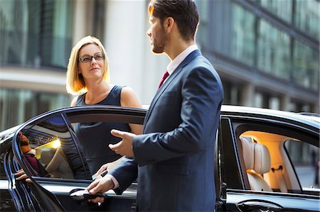 Chauffeur opening car door for businesswoman Stock Photo - Premium Royalty-Free, Code: 6113-07961628