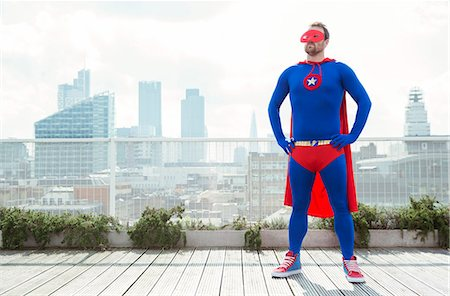 superhero - Superhero standing with hands on hips on city rooftop Stock Photo - Premium Royalty-Free, Code: 6113-07961740
