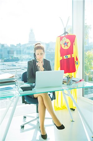 superhero - Businesswoman working at office desk with superhero costume behind her Stock Photo - Premium Royalty-Free, Code: 6113-07961741
