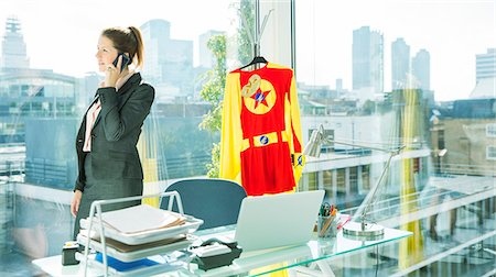 superhero - Businesswoman talking on cell phone with superhero costume behind her Stock Photo - Premium Royalty-Free, Code: 6113-07961742