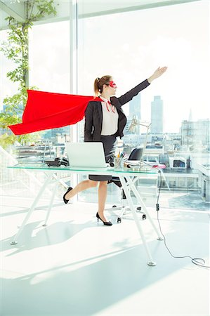 Businesswoman preparing to fly in cape and mask in office Stock Photo - Premium Royalty-Free, Code: 6113-07961746