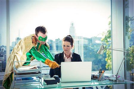 superhero - Superhero helping businesswoman working at office desk Stock Photo - Premium Royalty-Free, Code: 6113-07961750