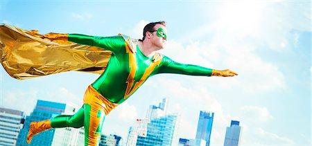 superhero - Superhero flying on city rooftop Stock Photo - Premium Royalty-Free, Code: 6113-07961713