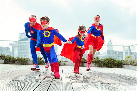 Superhero family playing on city rooftop Stock Photo - Premium Royalty-Free, Code: 6113-07961712