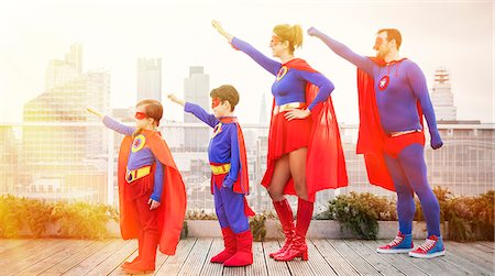 superhero - Superhero family standing with arms outstretched on city rooftop Stock Photo - Premium Royalty-Free, Code: 6113-07961716