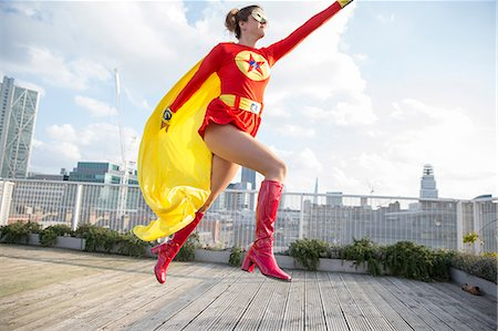 flying happy woman images - Superhero jumping on city rooftop Stock Photo - Premium Royalty-Free, Code: 6113-07961718