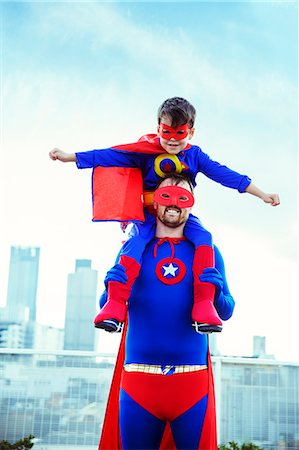 superhero - Superhero father carrying son on shoulders on city rooftop Stock Photo - Premium Royalty-Free, Code: 6113-07961719