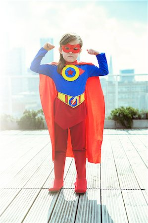 Superhero girl flexing muscles on city rooftop Stock Photo - Premium Royalty-Free, Code: 6113-07961721