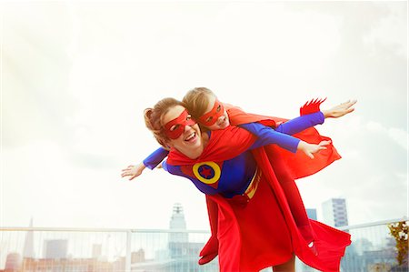 flying happy woman images - Superhero mother and daughter playing on city rooftop Stock Photo - Premium Royalty-Free, Code: 6113-07961722