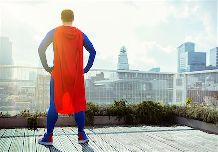 Superhero looking at view from city rooftop Stock Photo - Premium Royalty-Free, Code: 6113-07961727