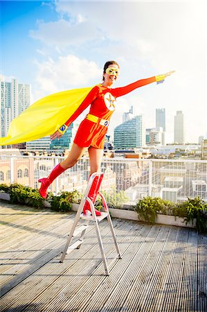 flying happy woman images - Superhero standing on stepladder on city rooftop Stock Photo - Premium Royalty-Free, Code: 6113-07961728