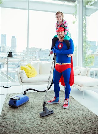 Superhero father vacuuming and carrying daughter on shoulders Stock Photo - Premium Royalty-Free, Code: 6113-07961731