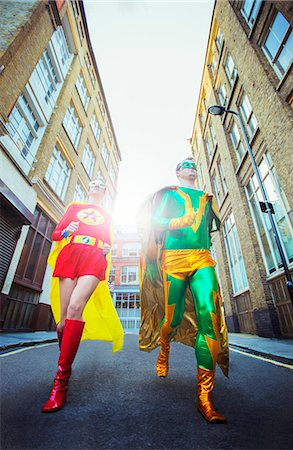 Low angle view of superhero couple running on city street Stock Photo - Premium Royalty-Free, Code: 6113-07961732