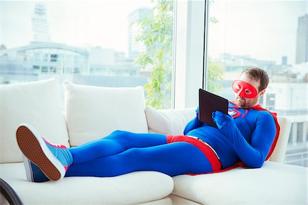 superhero - Superhero using digital tablet on living room sofa Stock Photo - Premium Royalty-Free, Code: 6113-07961734