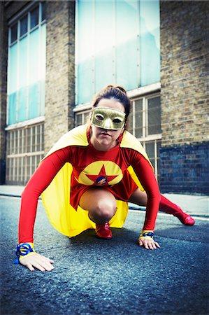 Superhero crouching on city street Stock Photo - Premium Royalty-Free, Code: 6113-07961736