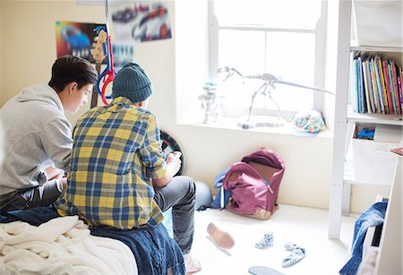Two teenage boys sitting on bed in messy room Stock Photo - Premium Royalty-Free, Code: 6113-07991965