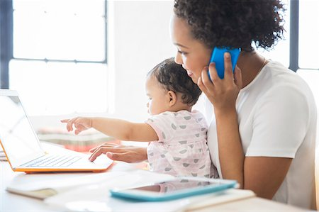 Mother working from home with daughter sitting on her lap Stock Photo - Premium Royalty-Free, Code: 6113-07992092