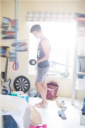 Teenage boy exercising with dumb bell in his room Stock Photo - Premium Royalty-Free, Code: 6113-07992000