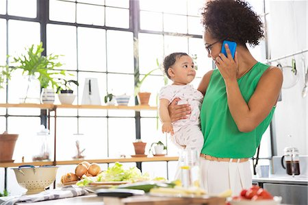 Mother holding her baby daughter while using mobile phone in kitchen Stock Photo - Premium Royalty-Free, Code: 6113-07992031