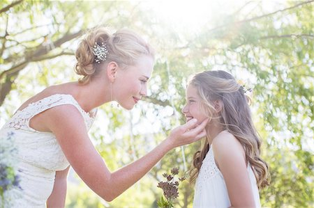 preteen touch - Bride and bridesmaid facing each other in domestic garden during wedding reception Stock Photo - Premium Royalty-Free, Code: 6113-07992154