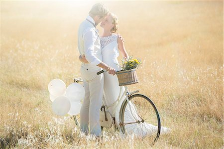 Young couple with bike kissing in meadow Stock Photo - Premium Royalty-Free, Code: 6113-07992164