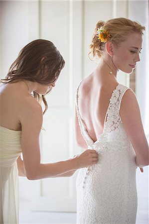 Bridesmaid helping bride with dressing in domestic room Stock Photo - Premium Royalty-Free, Code: 6113-07992174