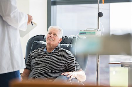 Doctor talking to patient receiving medical treatment in hospital ward Stock Photo - Premium Royalty-Free, Code: 6113-07905837