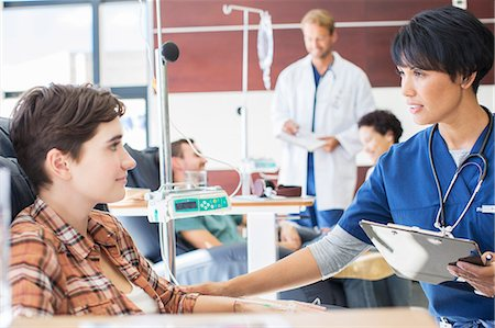 Female doctor holding clip board checking with female patient in outpatient clinic Stock Photo - Premium Royalty-Free, Code: 6113-07905952