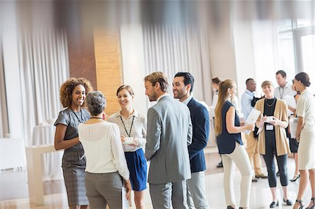 Group of business people standing in hall, smiling and talking together Stock Photo - Premium Royalty-Free, Code: 6113-07905999