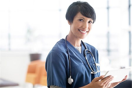 Portrait of female doctor with stethoscope around neck, holding digital tablet Stock Photo - Premium Royalty-Free, Code: 6113-07905909