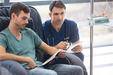 Doctor holding digital tablet, talking to patient undergoing medical treatment in hospital Stock Photo - Premium Royalty-Free, Code: 6113-07905914