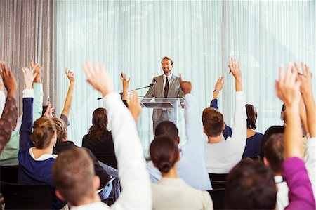 Businessman giving presentation in conference room, people raising hands Stock Photo - Premium Royalty-Free, Code: 6113-07906079