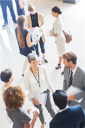 Businesswoman talking to conference participants, standing in lobby of conference center Stock Photo - Premium Royalty-Free, Code: 6113-07906087
