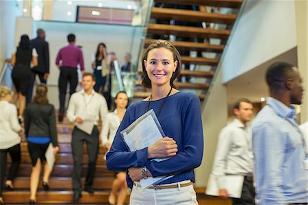 Portrait of smiling young woman standing in lobby of conference center Stock Photo - Premium Royalty-Free, Code: 6113-07906091