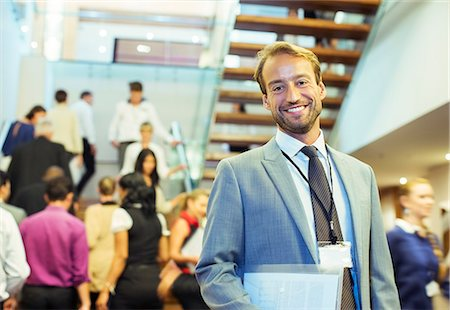 Portrait of smiling businessman holding file, standing in crowded lobby of conference center Stock Photo - Premium Royalty-Free, Code: 6113-07906094