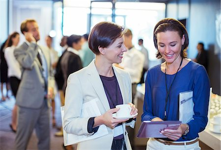 Portrait of two smiling women, talking in lobby of conference center during coffee break Stock Photo - Premium Royalty-Free, Code: 6113-07906099